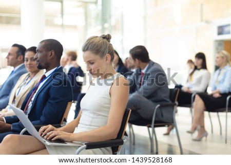 Side view of young Caucasian female executive using laptop in conference. Executives in the background.  room.  #1439528168