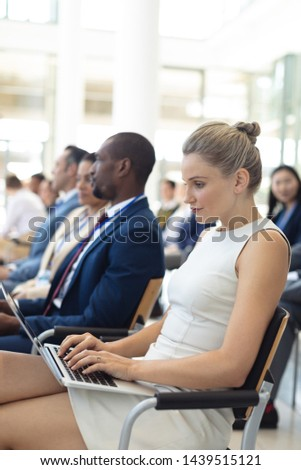 Side view of young Caucasian female executive using laptop in conference room. Executives in the background.  #1439515121