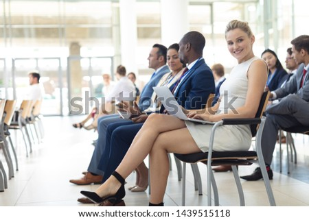 Side view of young Caucasian female executive using laptop in conference room, smiling to camera. Executives in the background.  #1439515118