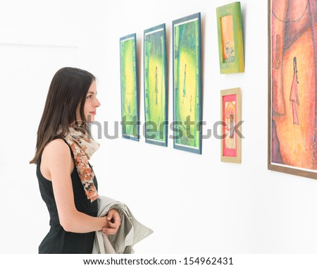 side view of young caucasian woman standing in an art gallery in front of colorful framed paintings displayed on a white wall