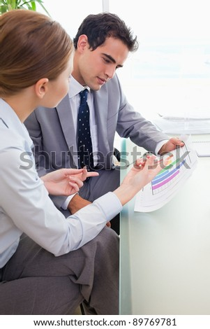 Side view of young colleagues analyzing diagram together