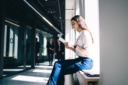 Side view of young concentrated ethnic female employee with long dark hair in classy clothes reading information on tablet while sitting on windowsill in modern office hall near walking colleagues