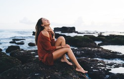 Side view of young ethnic lady in short summer dress sitting on rocky coast of Bali smiling and touching neck