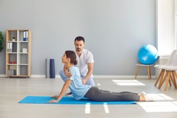 Side view of young female athlete doing back bending exercise during physiotherapy after sports injury. Health center specialist helping woman regain back flexibility after trauma