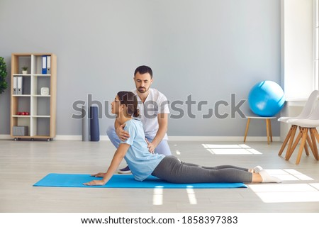 Side view of young female athlete doing back bending exercise during physiotherapy after sports injury. Health center specialist helping woman regain back flexibility after trauma Foto stock ©