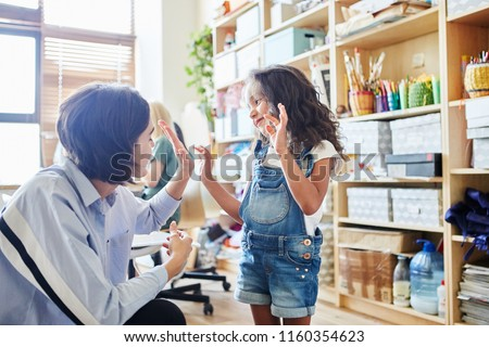 Side view of young female giving high five to adorable girl while teaching art in school #1160354623