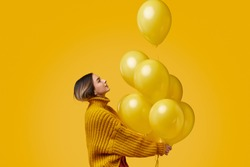 Side view of young female in knitted sweater looking up and releasing bunch of bright balloons during birthday party against yellow background