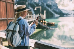 Side view of young female traveler with backpack and in warm wearing standing on quay against lake and looking at phone screen
