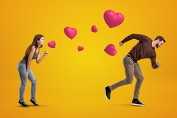 Side view of young girl following with her eyes young man who's running away being chased by cute valentine hearts that float in air on amber background. Young couple problems. St. Valentine's.