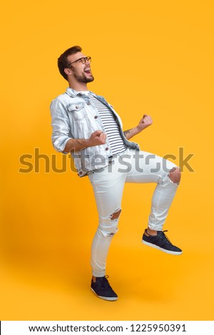 Side view of young guy in stylish outfit gesturing and screaming while standing on bright yellow background and celebrating success #1225950391