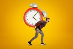 Side view of young handsome man carrying huge alarm clock on his back on yellow gradient background. Meet deadlines. Live in hectic world. Adjust to overbusy schedule.
