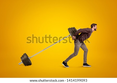 Side view of young handsome man in casual clothes carrying big bar-bell on amber background. Train your body. Exercise will power. Weightlifting equipment.