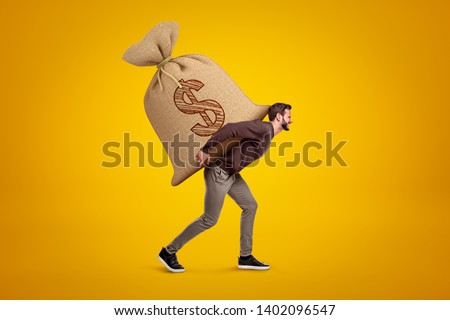 Side view of young handsome man in casual clothes carrying huge heavy sack with dollar symbol on. Avidity incarnate. Earn money. Become rich. Сток-фото ©