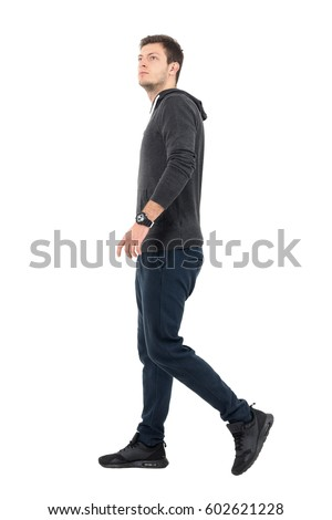 Side view of young handsome sporty man in sweatshirt and sweat pants walking looking up. Full body length portrait over white studio background. #602621228