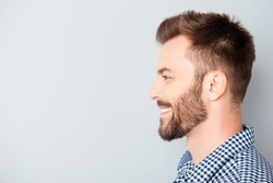 Side view of young happy smiling bearded man