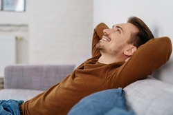 Side view of young hapy relaxed man sitting on sofa at home