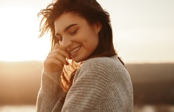 Side view of young long haired brunette in warm knitted sweater touching face and smiling while resting near lake at sunset time