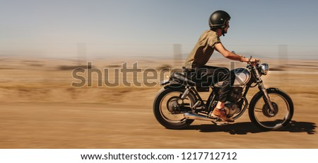 Side view of young man biker riding his bike on country road. Male rider driving motorcycle on a dirt road in country side.