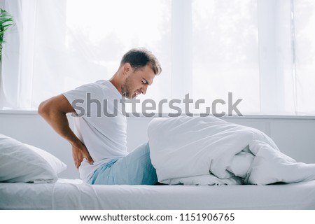 side view of young man in pajamas sitting on bed and suffering from back pain