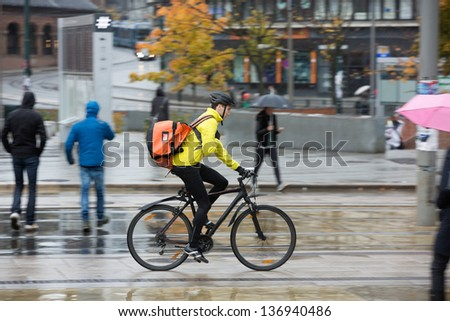 Side View Of Young Man In Protective Gear With Backpack Riding Bicycle On Street