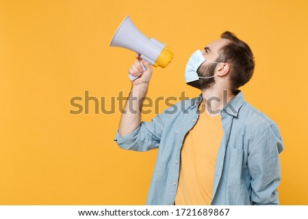 Side view of young man in sterile face mask posing isolated on yellow wall background studio portrait. Epidemic pandemic coronavirus 2019-ncov sars covid-19 flu virus concept. Scream in megaphone