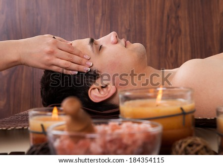 Side view of young man receiving head massage from massager in spa