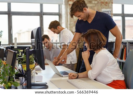 Side view of young man standing next to his woman colleague pointing at something on laptop screen, working together in office #566369446