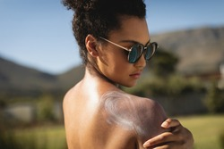 Side view of young mixed race woman applying sunscreen on shoulders in backyard of home on a sunny day