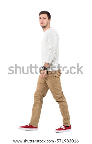 Side view of young modern stylish man walking and looking at camera. Full body length portrait isolated over white studio background.  #571983016