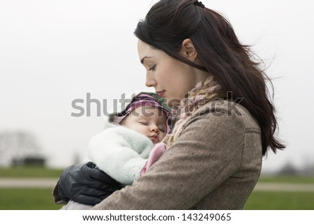 Side view of young mother carrying sleeping baby at park