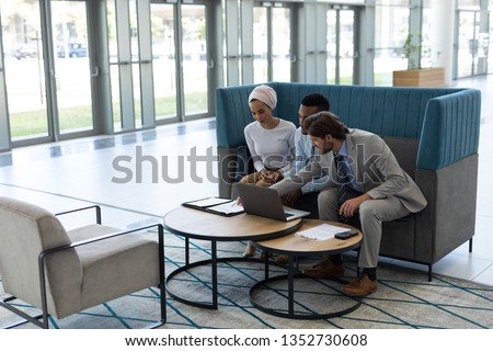 Side view of young multi-ethnic business people discussing over laptop in the lobby at office #1352730608