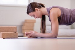 Side view of young purposeful caucasian pretty woman doing plank exercise on floor in bright and comfortable gym. Concept of regular training and healthy lifestyle. Advertising space