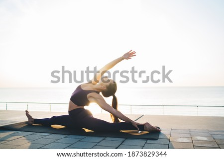 Side view of young slim woman in sports top and leggings stretching on mat and doing Exalted Crescent pose on twine  while practicing yoga on embankment against sea Foto stock ©