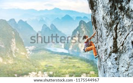 side view of young slim woman rock climber in bright orange pants climbing on the cliff against a high mountains. girl climbs on a vertical flat rocky wall and making hard move. Copy space #1175544967