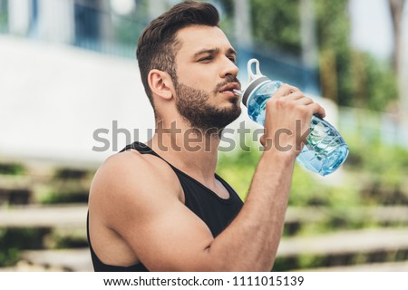 side view of young sportsman drinking water from bottle  #1111015139