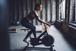 Side view of young sporty female in activewear spinning on stationary bike in loft styled gym and listening to music through earphones
