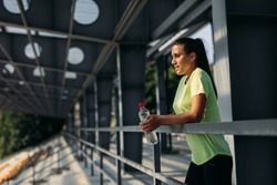 Side view of young sporty woman in yellow t-shirt with bottle of water in hands resting after training. Modern local stadium. Outdoors activity.
