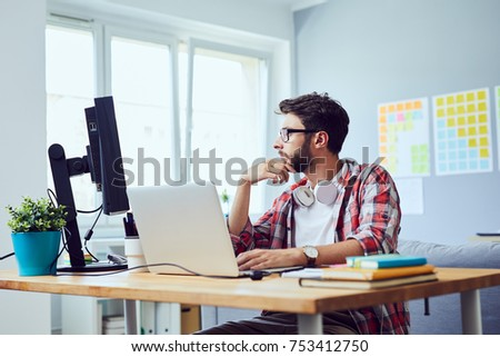 Side view of young web developer looking at screen and thinking about work project