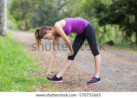 Side view of young woman exercising on footpath in forest #570755665