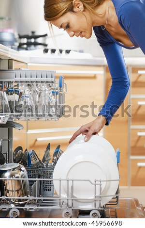 side view of young woman in kitchen doing housework