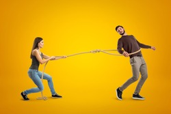 Side view of young woman lassooing young man on yellow background. Predator - prey relationship. Emotional immaturity. Rush into marriage.