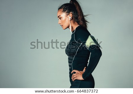 Side view of young woman listening to music with earphones. Fit female model standing with her hands on hips against grey background.