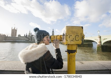 Side view of young woman looking through telescope by river Thames; London; UK
