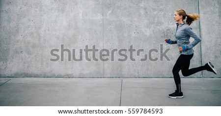 Side view of young woman running on sidewalk in morning. Health conscious concept with copy space.