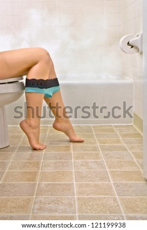 Side view of young woman sitting in bathroom