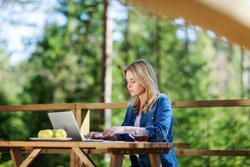 Side view of young woman working on laptop computer sitting at wooden table on balcony of countryside house