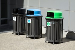 Side view on a row of trash receptacles, with a compost and recycling bin beside a garbage can along a wall outside of an office building