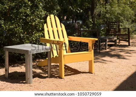 Side view on a yellow adirondack patio chair beside a metal table, in a bright outdoor patio and garden