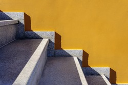 Side view on bright yellow or mustard painted wall and white marble stairs. Geometrical pattern, straight lines, light and shadow contrast. Graphic art, modern design, urban architecture. Copy space.