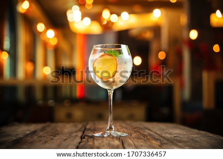 Side view on fresh cool cocktail gin tonic with a slice of orange and ice in a wine glass on the woden table, horizontal format Foto stock ©